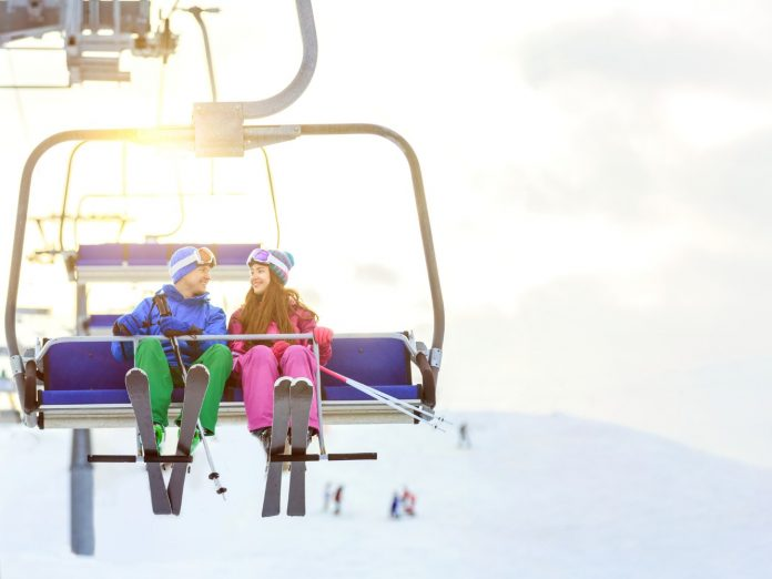 two people sitting on a chairlift