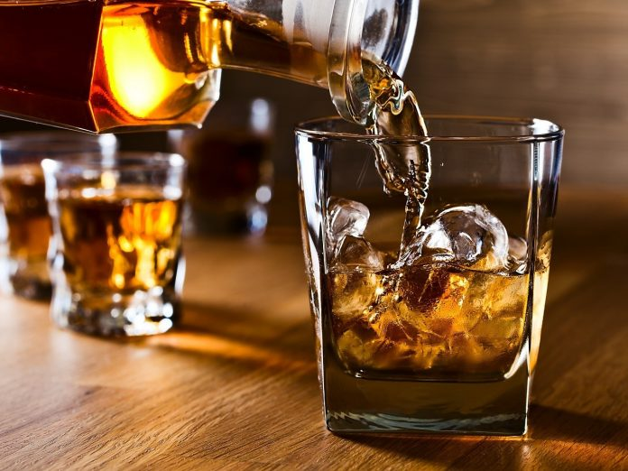 whiskey being poured into three glasses
