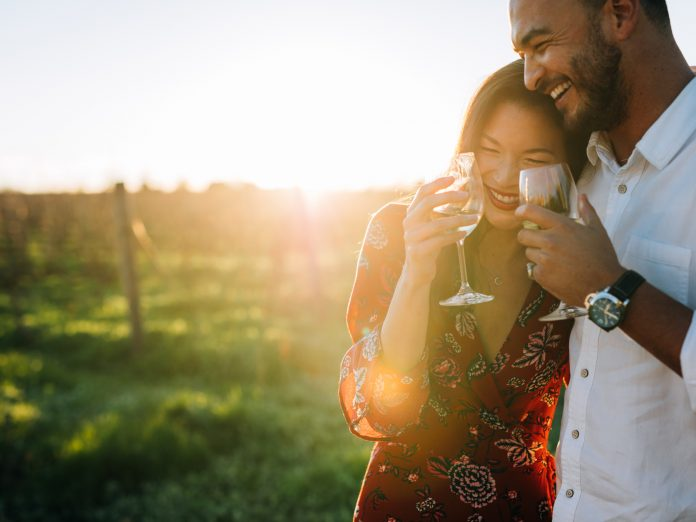 a couple with a glass of wine at a vineyard