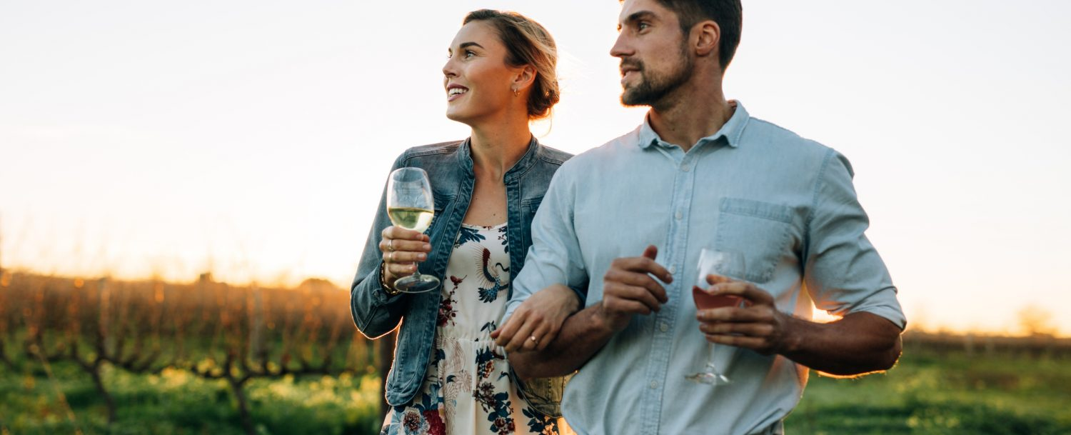 couple in vineyard holding wine glasses