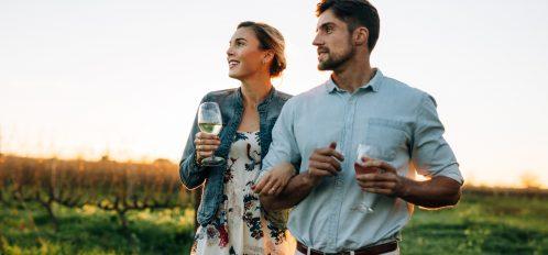 couple in vineyard holding wine glasses
