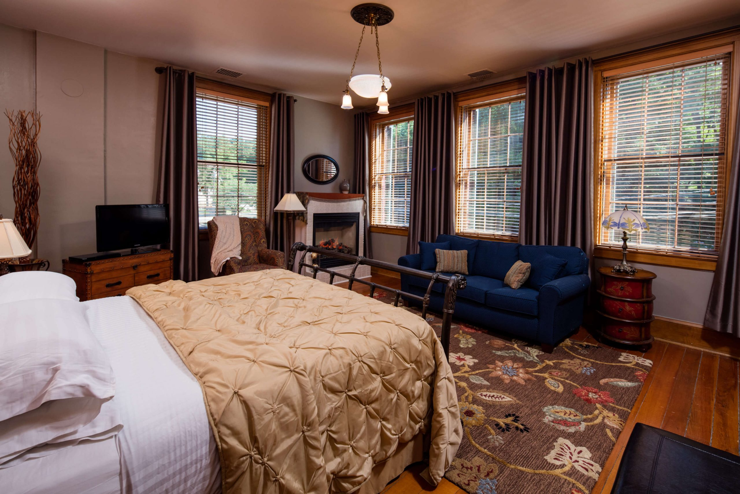 bed, fireplace, rug, windows, couch in Julia suite
