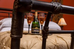wine bottle and glasses on tray on bed