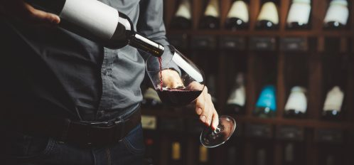 Close up shot of sommelier pouring red wine from bottle in glass on underground cellar background